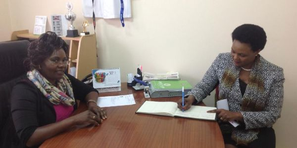 Vice-Chancellor, Karatina University,  (right) signing visitors book in JKUAT University Librarian's Office when she paid a courtesy call