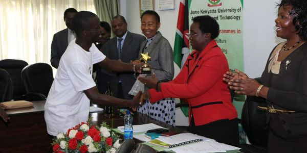 Otieno Ochieng Director of Igiza Arts Group presents the Emerald Best User Institution Trophy to JKUAT VC Prof Mabel Imbuga as Prof Kahangi (to VC's right)  and Dr Mangi'ra (to VC's left) applaud