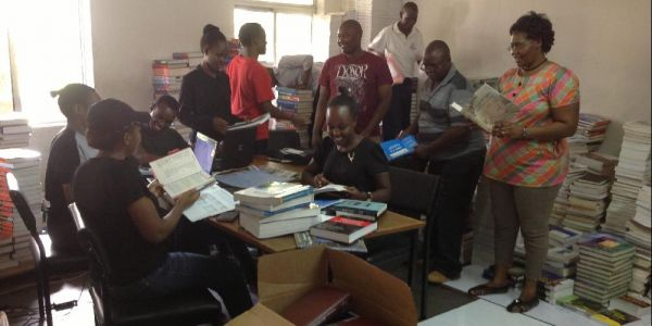 From right (standing) Dr. R. Mangira,  Mr. J. Ngugi and Mr. Wafula Kimani with the campus team sorting out books donated by Books for Africa