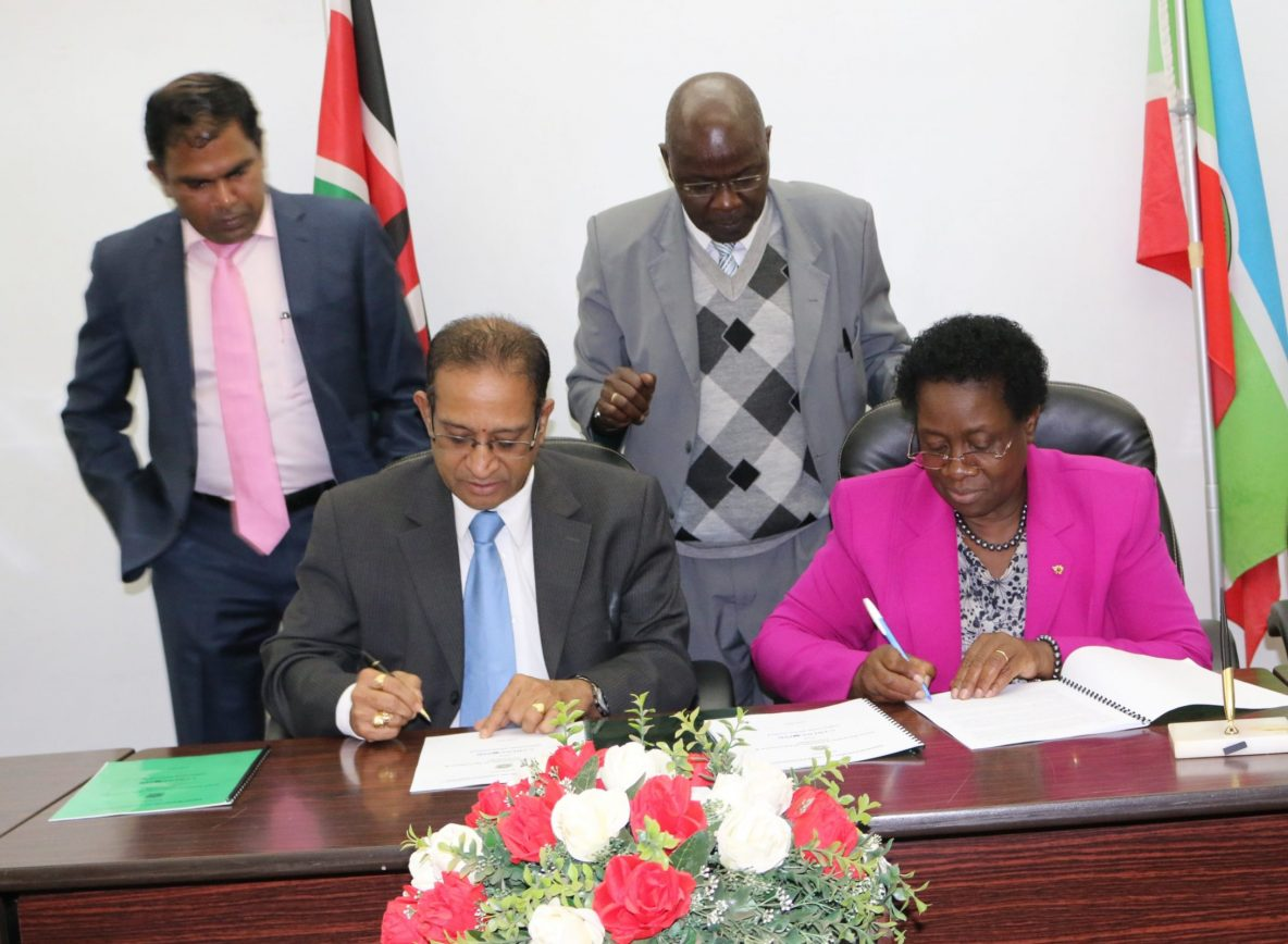 Prof. Imbuga (right) and Mr. Manian sign the MoU between JKUAT and CyberComb. Looking on is Mr. Dash (Left) and JKUAT Director Linkages, Dr. Mwikamba Kaibui