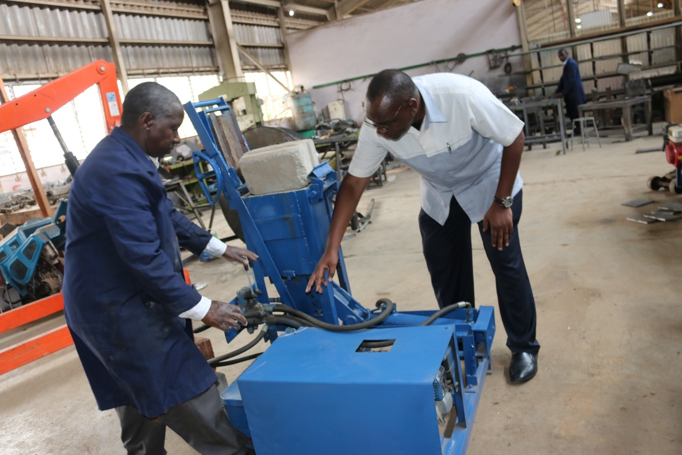 Prof. Obanda (right) is taken through the block press machine, by Eng. Ng'ang'a, the inventor
